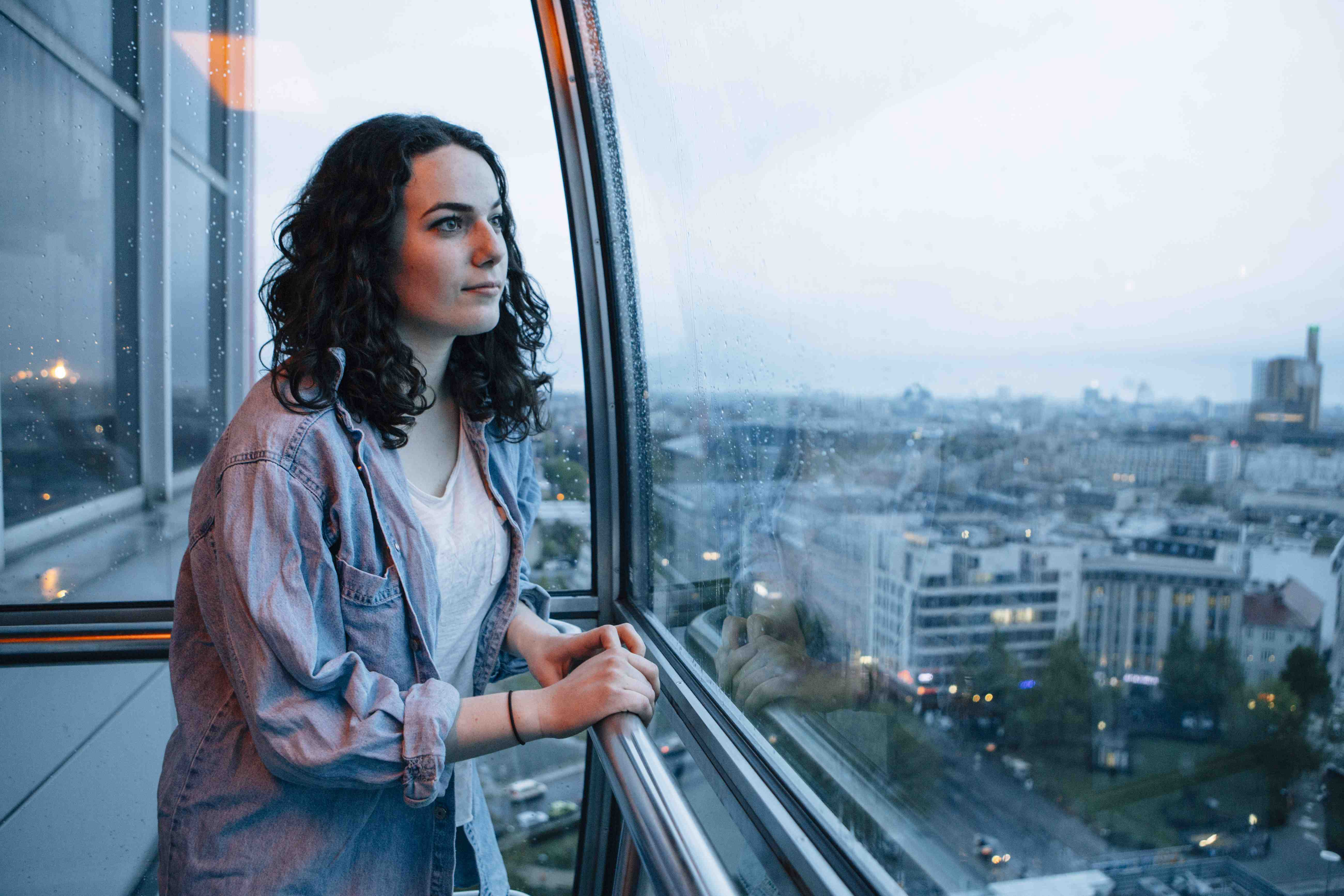woman stands in futuristic glass elevator looks at skyline